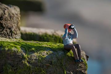 Miniatur Figur Mann sitzt im Gras und schaut durch ein Fernglas (no brand)