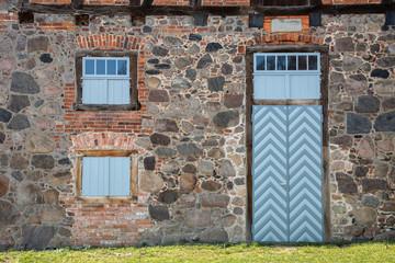 Fassade einer Scheune mit alten Ornamenten in Fenster und Tür