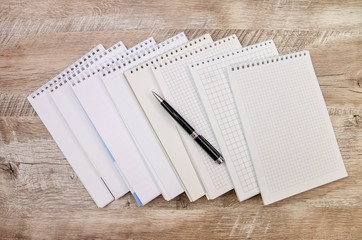 many white notebooks and a pen on a wooden background
