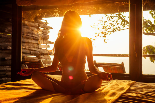 woman sun rays in the form of chakras in tropical yoga studio a view outside to the hills while sunset.girl in eco hotel panoramic windows enjoying solitude with nature Kerala India wildernest resort