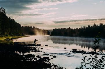 Angler am Fluss im Sonnenaufgang