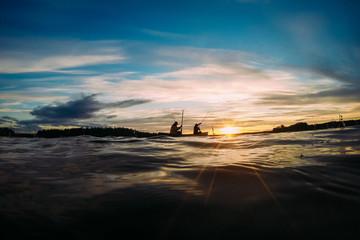 Zwei Angler im Kanu auf See im Sonnernuntergang