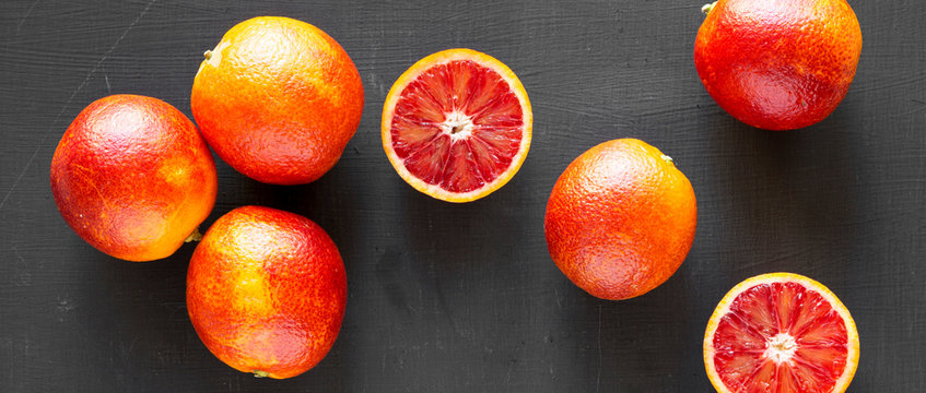 Whole and halved blood oranges on black background, top view. Flat lay, overhead, from above. Close-up.