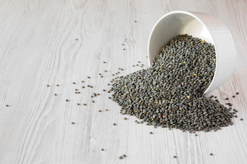 Green french lentils in gray bowl over white wooden background, side view. Close-up.