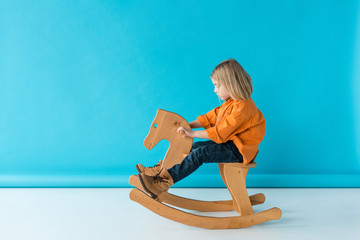 side view of blonde and cute kid riding on rocking horse on blue background
