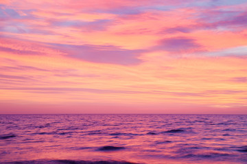 Small, blurry waves of sea and burning purple pink sunset sky. Peaceful atmosphere at beach. Nice nature background.