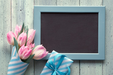 Chalk board with pink tulips and wrapped gift boxes. Flat lay with text space