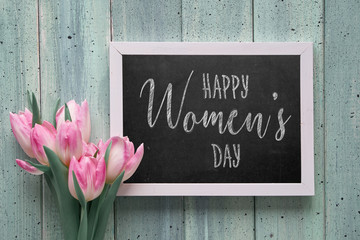 """Chalk board with text """"Happy Women's day"""" and pink tulips, flat lay on light green boards."""