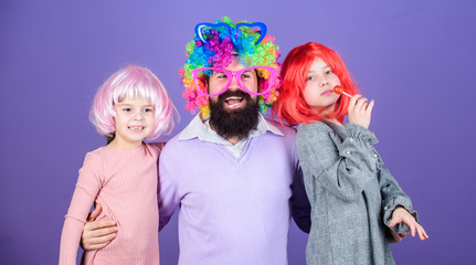 Best dad ever. Father hug daughters. Just for fun. Party time. How crazy is your father. Man bearded father and kids girls wear colorful wig violet background. Friendly family wear party accessories