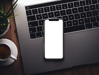 Smartphone on laptop keyboard blank screen