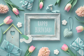"""Turquoise paper springtime background with pink flowers, wrapped gift boxes and wooden frame with text """"Happy Birthday""""."""