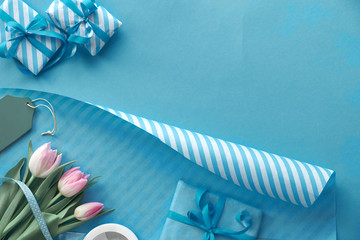 Blue background with pink tulips, stripy wrapping paper and gift boxes, copy-space