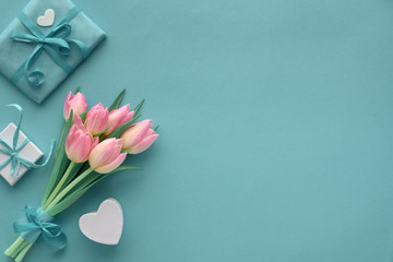 Springtime turquoise paper background with pink tulips and wrapped gifts, copy-space