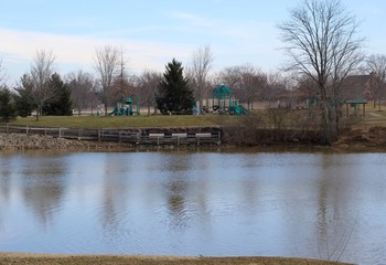 The lake and the playground in the park on a sunny day.