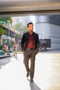 Young handsome Hispanic businessman thinking and walking outside the office building