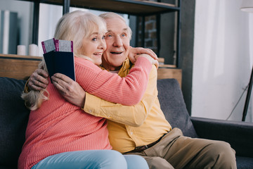 happy senior couple hugging and holding air tickets with passports at home