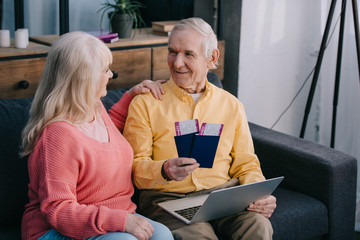 happy senior couple holding air tickets with passports while sitting on couch at home