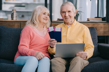 smiling senior couple holding air tickets, laptop and passports while sitting on couch at home