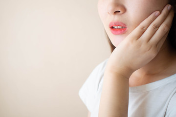 Young woman suffering from toothache over white background. Cause of tooth pain include tooth decay, inflammation, dental abscess, gum disease or sensitive teeth. Dental health concept. Close up.