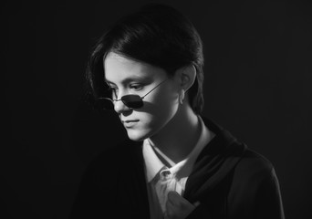 Serious, beautiful girl with short hair sitting in sunglasses under bright light on dark background