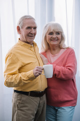 smiling senior couple in casual clothes with cup of coffee at home