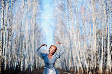 Beautiful young girl of European appearance with red hair and blue eyes on the background of spring birch forest. Bright woman. Illustration to a book or a fairy tale.