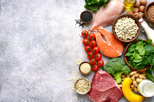 Assortment of healthy protein sources and body building food : meat, fish, fruits, vegetables, legumes, nuts, cereals and dairy products.Top view with copy space.
