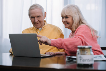 smiling senior couple sitting at table, pointing with finger and using laptop
