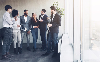 Business team talking at coffee break near window