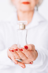 Senior lady lifestyle. Fragrance choice. Bottle of expensive perfume in female hands.