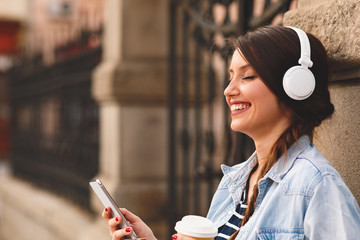 Young woman listens to music via headphones and smartphone in the city