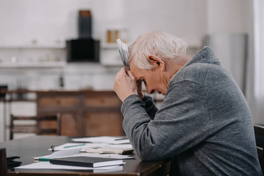 stressed senior man in casual clothes sitting at table with paperwork and holding money at home