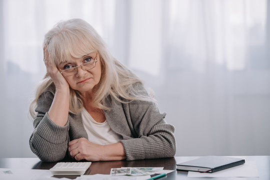 senior woman sitting at table with money, looking at camera and having headache