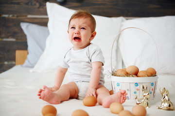 Crying baby celebrating Easter morning in bed
