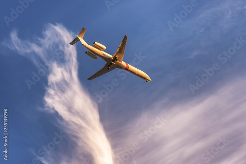 Airplane in the sky at sunset with landing lights on