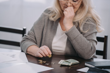 cropped view of female pensioner sitting at table and counting money at home