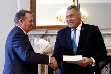 Britain's International Trade Secretary Liam Fox signs a trade continuity agreement with the Pacific Islands, as the government seeks a Brexit solution, in London