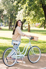 cheerful young woman smiling while riding bicycle in park