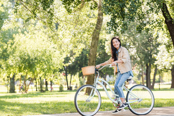 happy pretty girl smiling while riding bicycle in park