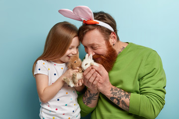 Funny bearded ginger man tells story about Easter bunny to daughter, play with two fluffy decorative rabbits, have happy expressions, rejoice having new pets at home. Family and animals concept