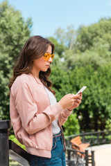 attractive girl in sunglasses using smartphone while standing in park