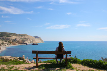 A woman is sitting on a wooden bench and looks at Petra-tou-Romiou - birthplace of Aphrodite on Cyprus, view from nature trail Petra-tou-Romiou
