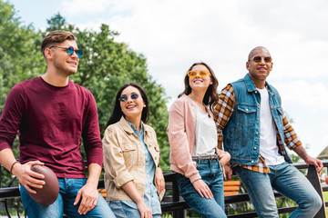 cheerful multicultural young men in sunglasses standing with longboard and american football near attractive girls
