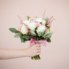 pink wedding bouquet in the bride's hand on the wall background, isolated