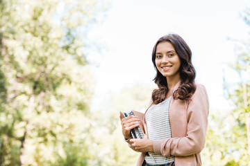 beautiful young woman holding books and smiling in park