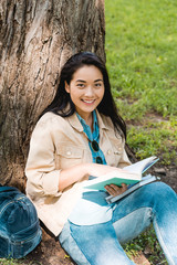 pretty student smiling while sitting in park with books