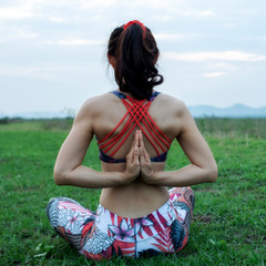 young woman practicing yoga, lotus position, and meditating in nature