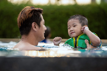 Happy family enjoying swimming time in pool at summer vacation.