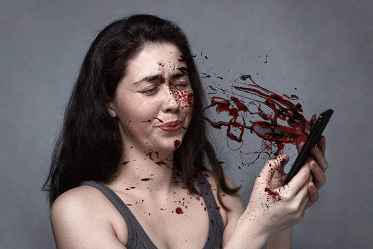 The concept of social problems, spam, support, suicide, dangerous driving . The young girl blinked in sudden fright, the phone in her hands splatters with blood