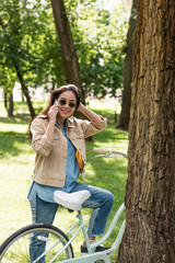 cheerful young woman in sunglasses talking on smartphone near bike in park